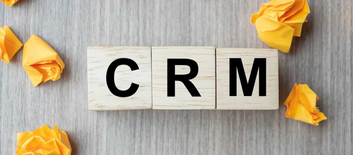 wooden cube with CRM text (Customer Relationship Management) and crumbled paper on table background. Financial, marketing and business concepts