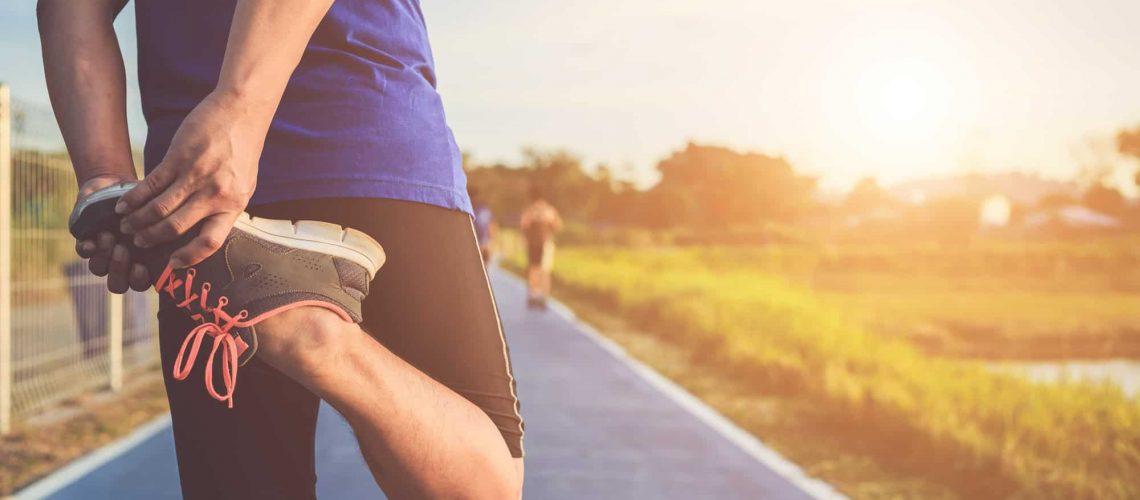 asian-runner-warm-up-his-body-before-start-running-road